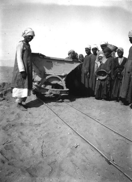 Workmen and children next to a mine truck