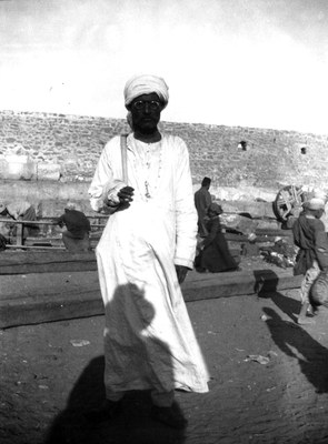 Man in white tunic and spectacles