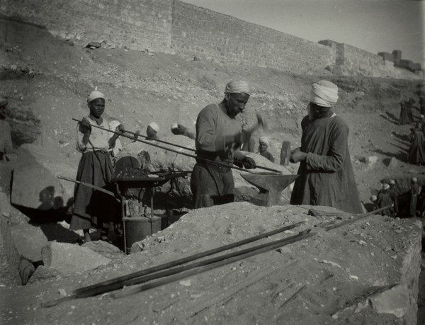 Local workmen hammering an iron bar