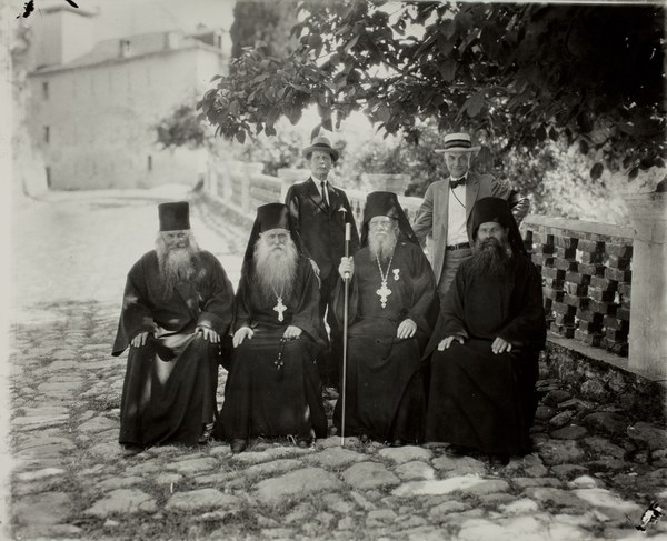 Four seated monks, Thomas Whittemore (left), and George D. Pratt (right)