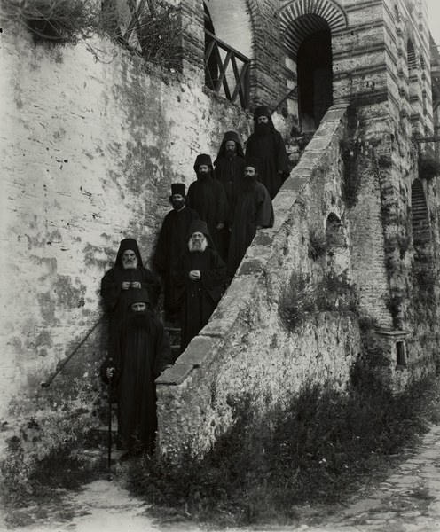 Monks and the Abbot standing on the exterior stairway