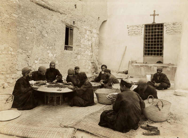 Monks sorting dried grapes